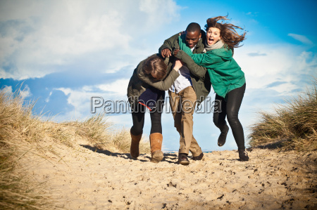 young adult friends running in sand