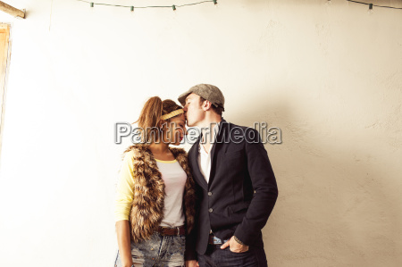 couple by wall man kissing womans