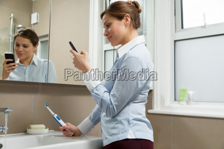 young woman using cell phone holding