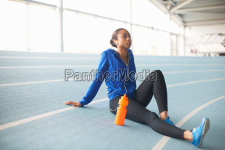 young female athlete wearing earphones resting