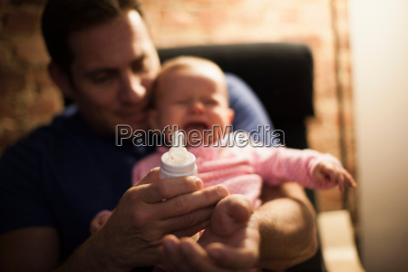 father feeding crying baby daughter