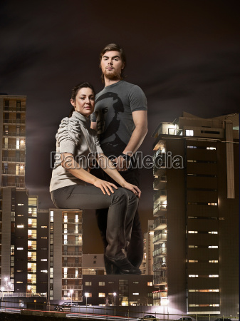 oversized couple sitting on buildings