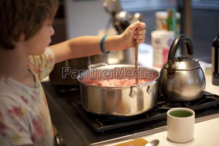 boy stirring pan of food on