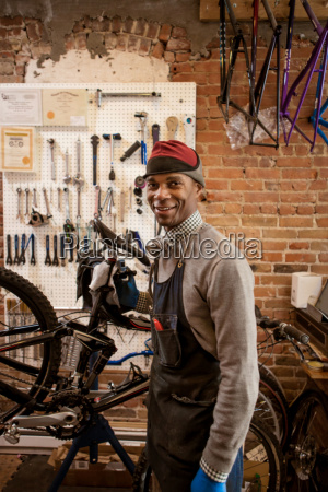satisfied mechanic holding up bicycle