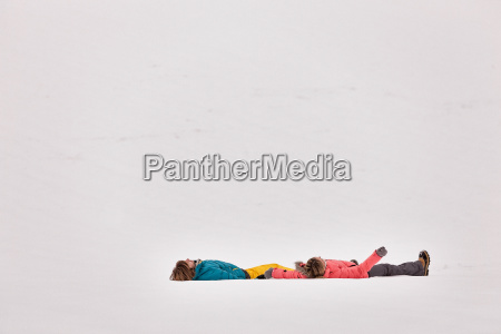 couple lying on backs in snow