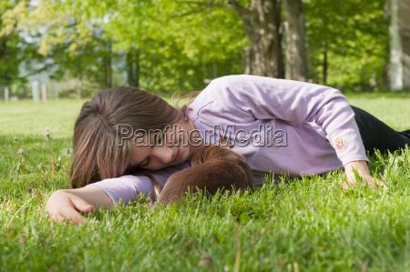 adolescent cuddling puppy