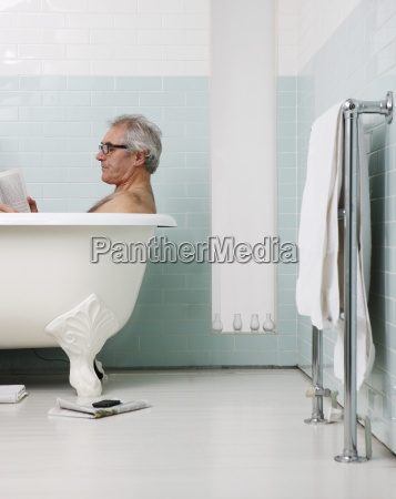 senior man bathing and reading book