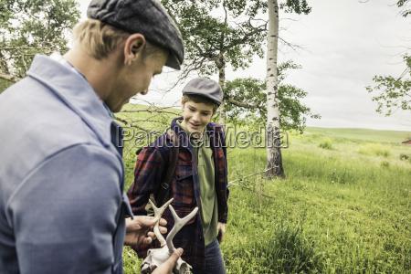 boy and man holding animal skull