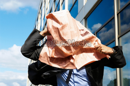 businessman with newspaper over face