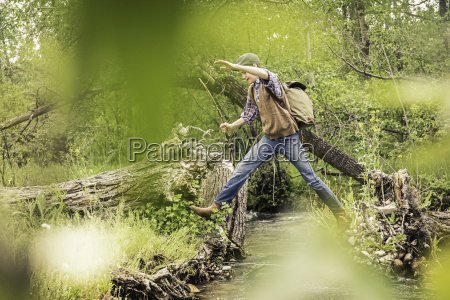 teen boy with backpack jumping across