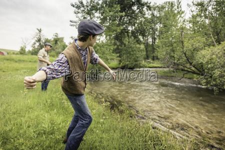 man and boy on riverbank wearing