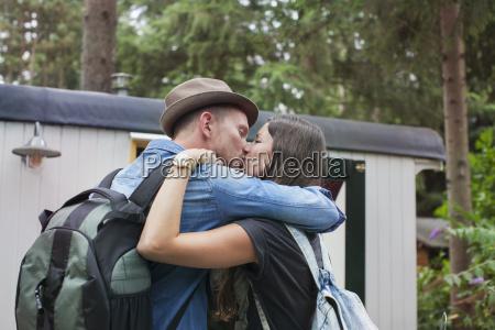 romantic couple kissing on cabin porch