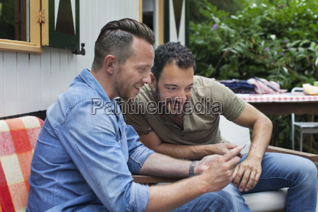 two men reading smartphone texts on