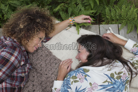 two female friends lying gossiping on