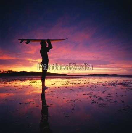 surfer standing on beach at sunset