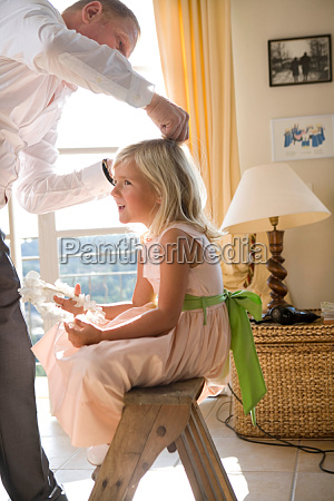 father prepares girls hair