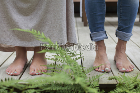 painted toenails of couple standing on