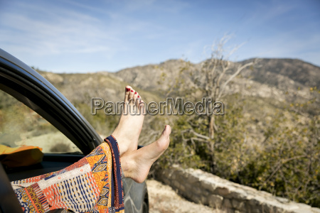 young womans feet sticking out car
