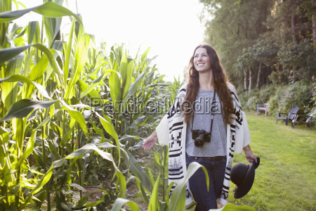 young female photographer strolling in field