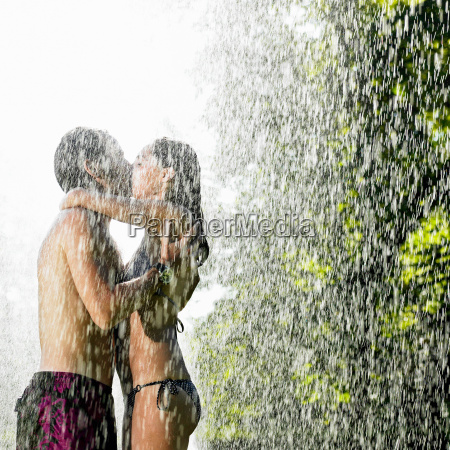 couple kissing under a water jet