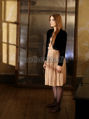 young woman standing by mirror