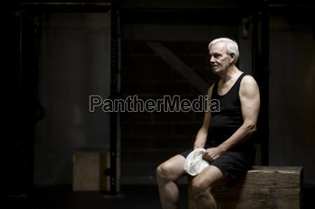 senior man sitting resting in dark
