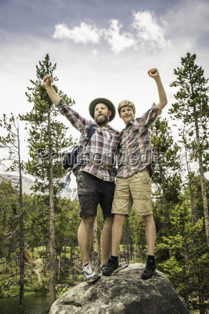 father and son in forest standing