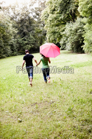 couple running through grassland