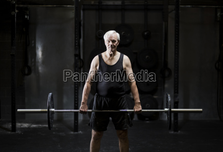 senior man weightlifting barbell in dark