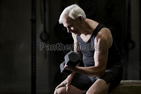 senior man sitting doing bicep curls