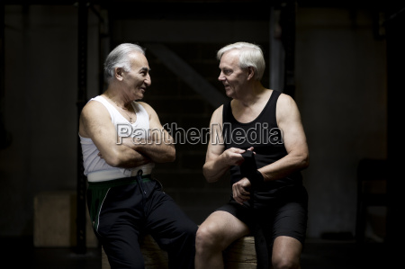 two senior men chatting and preparing