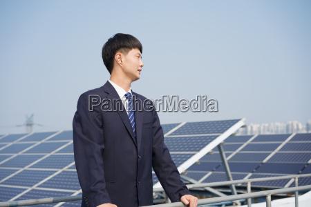 businessman, on, roof, of, solar, panel - 19479920