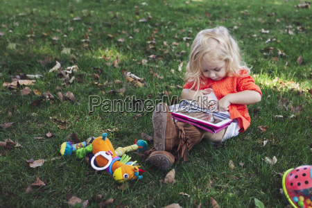 girl sitting on grass with toys