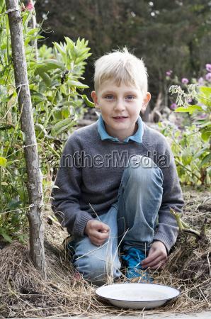 portrait of boy kneeling in organic