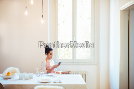 young housewife wearing apron at table