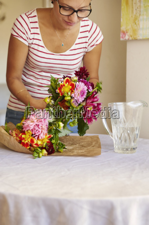 mid adult woman unwrapping flowers in