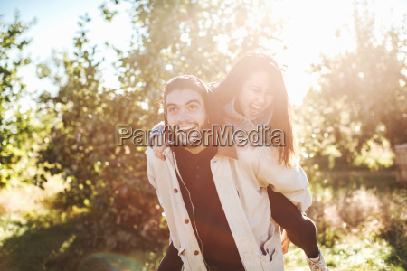 young man giving young woman piggyback