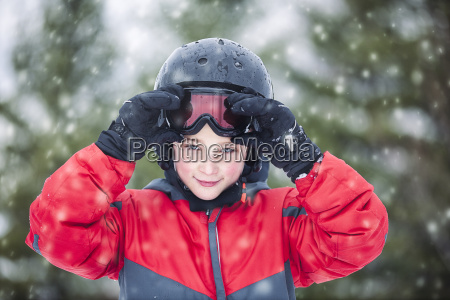 boy wearing helmet and skiing goggles