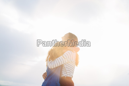 two young female friends hugging at