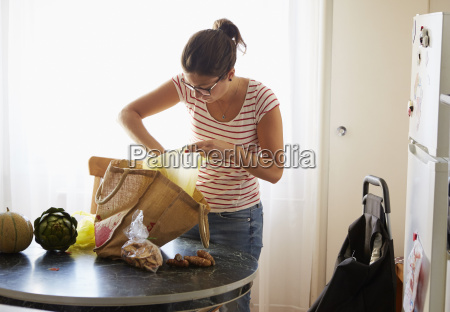 mid adult woman unpacking food shopping