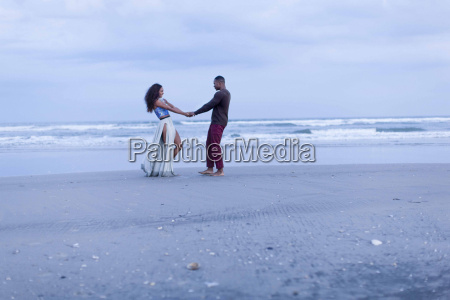 couple fooling around on beach holding