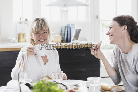 two mature women sitting at kitchen