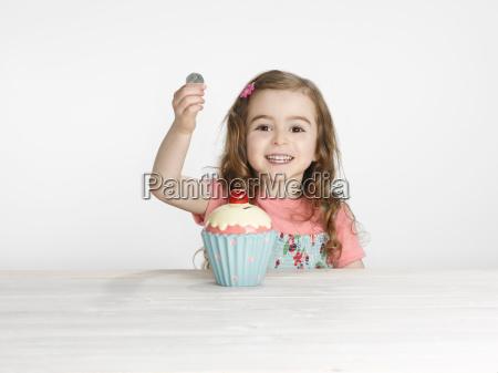 girl putting coins in cupcake jar