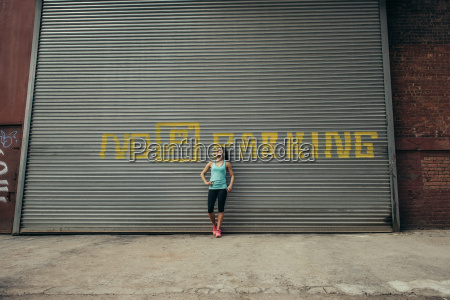 young female runner leaning against shutter
