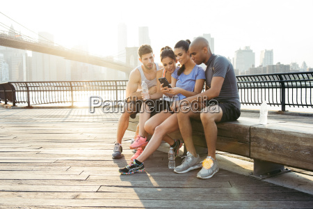 four adult running friends reading smartphone