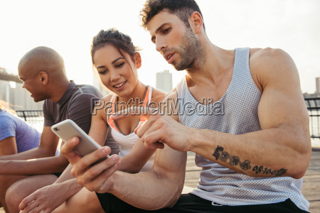 young adult running friends using smartphone