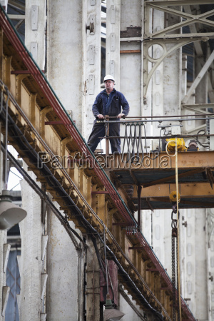 worker on gantry in shipyard workshop