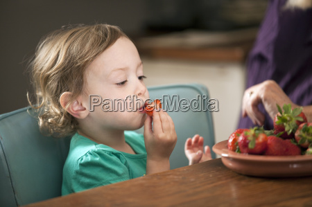 girl sitting eating bowl of strawberries