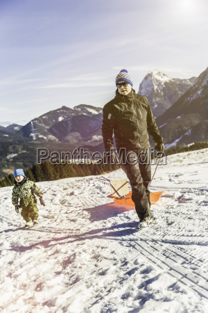 man pulling sled on snow achenkirch