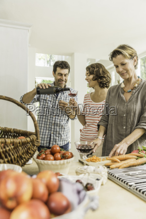 three adults pouring red wine whilst